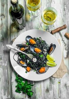 Massa mediterrânea. espaguete com tinta de choco, amêijoas e vinho branco. sobre uma superfície rústica.