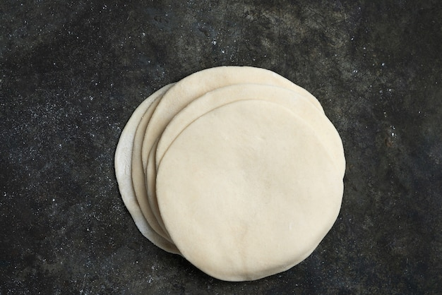 Massa não cozida enrolada para chapati de pão achatado indiano. pronto para cozinhar o conceito. refeições fáceis. comida caseira. camada plana da vista superior