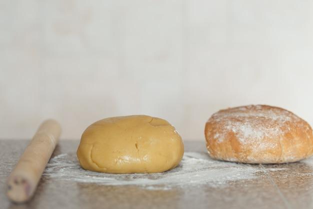Massa, pão com farinha em cima da mesa.