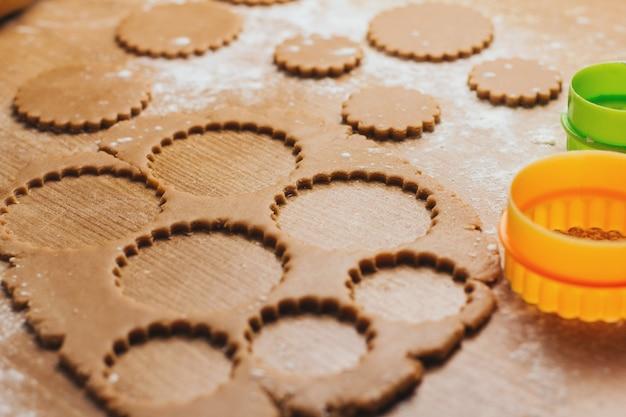 Massa para biscoitos de gengibre em uma mesa polvilhada com farinha. cortando biscoitos redondos.