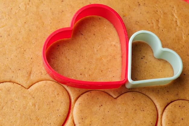 Massa para fazer biscoitos em forma de coração no dia dos namorados. pastelaria caseira. plástico vermelho e verde