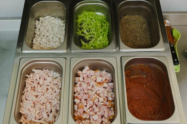 Massa para pizza com ingredientes preparados para cozinhar pizza em um restaurante