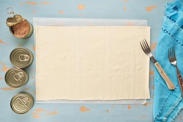Massa para preparar empanada recheada de atum em uma mesa de madeira azul e latas de atum