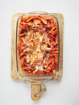 Massa pene italiana com molho de tomate e queijo parmesão gratinado em assadeira de vidro e tábua de cortar de madeira.