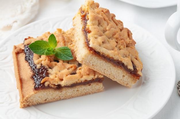 Massa quebradiça e torta de geleia de maçã caseiras em um prato branco estão duas peças quadradas decoradas com um raminho de hortelã close up fundo branco