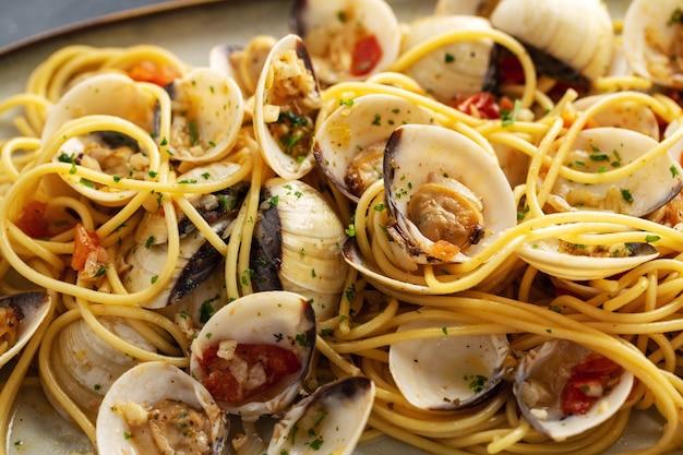 Massa saborosa apetitosa do marisco do alle vongole dos moluscos caseiros frescos com alho e vinho branco na placa. fechar-se.