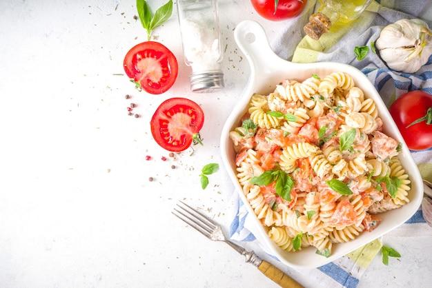 Massa vegana saudável da dieta da primavera. massa fusilli italiana com tomate, vegetais verdes, ervas frescas, cream cheese ou queijo feta, no espaço de cópia de fundo de mesa branca