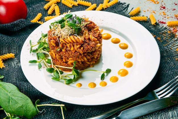 Massa vegetariana à bolonhesa com molho vermelho e carne de soja. macarrão decorado com microgreen em um prato branco em uma composição com legumes