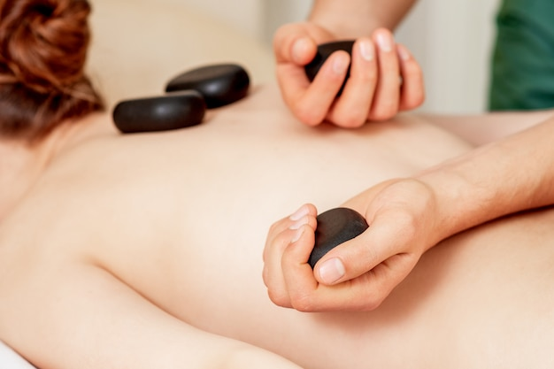 Massageador colocando pedras nas costas.