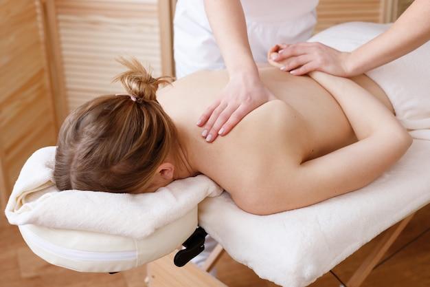 Massageador faz massagem nas costas da mulher