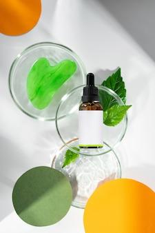 Massageador gua sha para o rosto com soro de hidratação natural oilpetri pratos com folha verde e água
