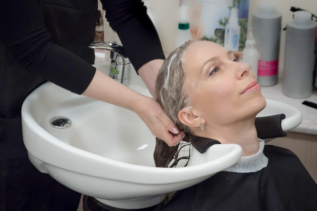 Massageando couro cabeludo e cabelo com shampoo. lavagem de cabelos no salão.