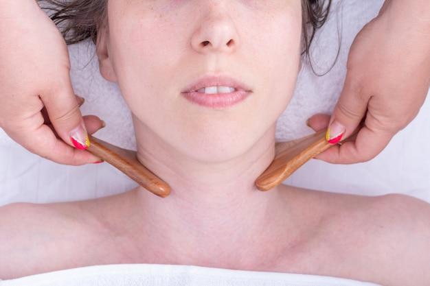 Massageie o pescoço da menina com um massageador natural de madeira, close-up. cuidados com o rosto e pescoço. massagem facial de drenagem linfática com massageador de madeira