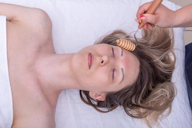 Massageie o rosto da garota com um massageador de rolo de madeira, close-up. cuidados com o rosto e pescoço. massagem facial de drenagem linfática com massageador de madeira