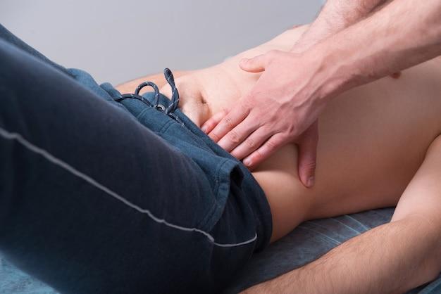 Massagem cinesiológica feita na parte inferior da barriga de um paciente do sexo masculino.