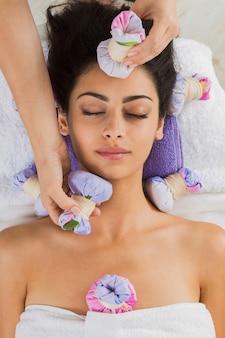 Massagem com ervas à bola no centro de bem-estar do spa ayurveda