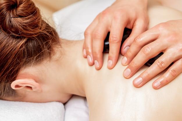 Massagem com pedras nas costas da mulher