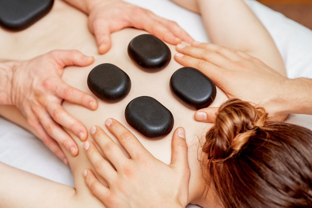 Massagem com pedras nas costas da mulher.