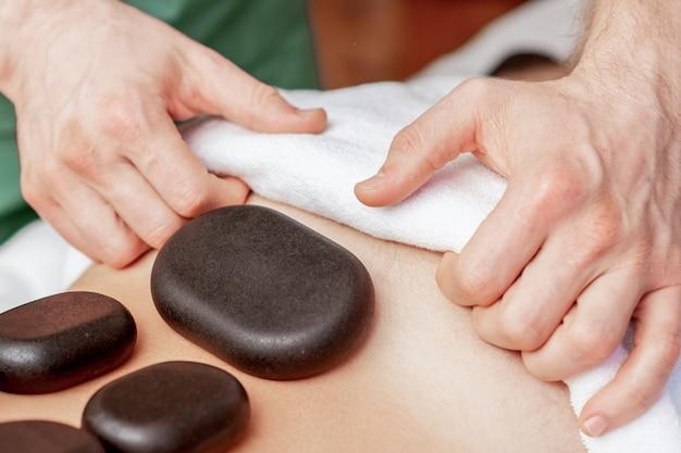 Massagem com pedras nas costas do homem.