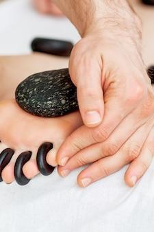 Massagem com pedras nos dedos dos pés