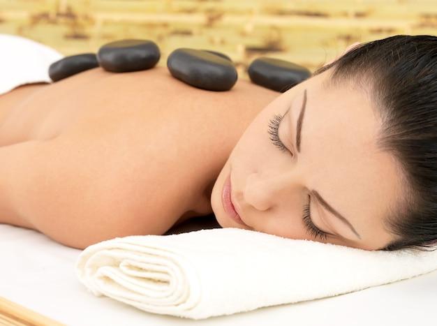 Massagem com pedras para jovem em salão de beleza spa. terapia recreativa.