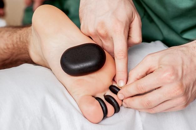 Massagem com pedras quentes nos dedos dos pés.