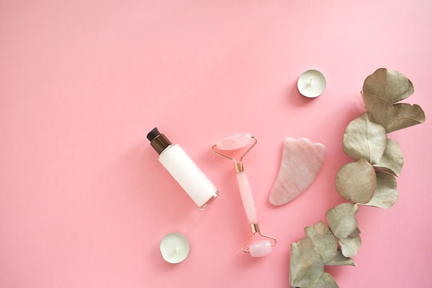 Massagem com rolo de quartzo para o rosto com jade natural rosa. ferramenta de massagem guache, com óleo de soro de beleza. anti-envelhecimento e lifting em casa. massagem de cuidado facial e conceito de relaxamento.