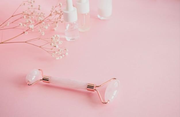 Massagem com rolo de quartzo para o rosto com jade natural rosa. ferramenta de massagem guache, com óleo de soro de beleza.