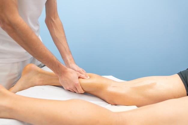 Massagem da panturrilha a um atleta por um fisioterapeuta profissional