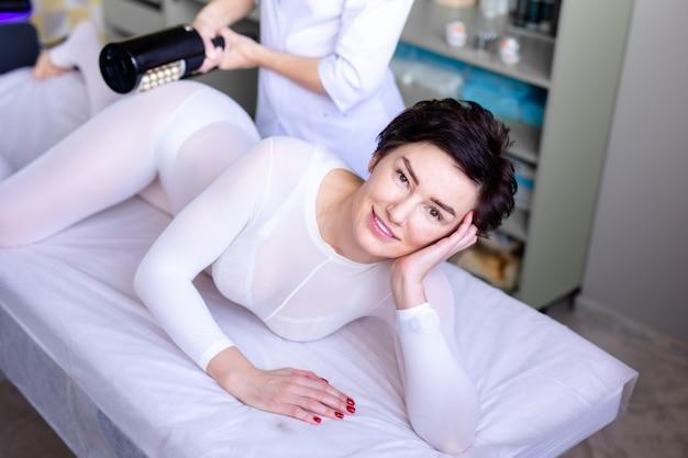 Massagem de drenagem linfática lpg ou processo de aparelho r-elegante. mulher de terno branco, recebendo massagem anticelulite em um salão de beleza. cuidados com a pele e o corpo.