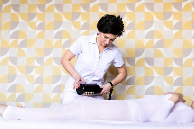Massagem de drenagem linfática lpg ou processo de aparelho r-lustroso. mulher de terno branco, recebendo massagem anticelulite em um salão de beleza. cuidados com a pele e o corpo.