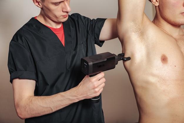 Massagem de percussão de arma de esportes na sala médica do ginásio. massagista faz exercícios de massagem em casa. terapia de percussão para massagem regeneradora do corpo desportivo. conceitos de reabilitação de lesões. copie o espaço