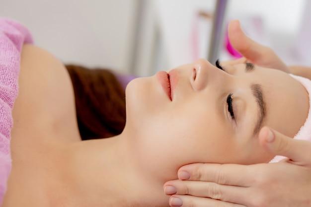 Massagem de rosto. close-up de jovem recebendo tratamento de massagem spa no salão de beleza spa. cuidados com a pele e o corpo. tratamento de beleza facial.