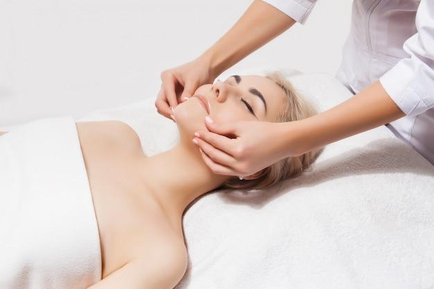 Massagem de rosto. close-up de uma jovem mulher recebendo massagem spa em um salão de beleza e spa por esteticista. cuidados com a pele e corpo do spa. cuidados com o rosto de beleza. cosmetologia.