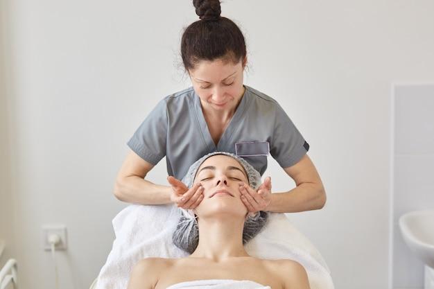 Massagem de rosto, pessoas, beleza, spa, estilo de vida saudável e conceito de relaxamento. fechar o retrato de mulher jovem e bonita deitada na boca
