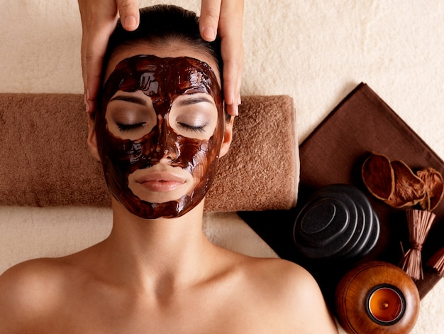 Massagem de spa para jovem com máscara facial no rosto - dentro de casa