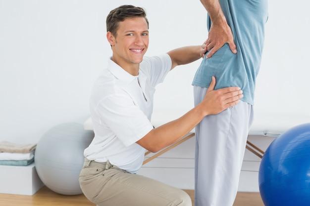 Massagem de terapeutas masculinos equipa a parte inferior das costas no hospital de ginásio