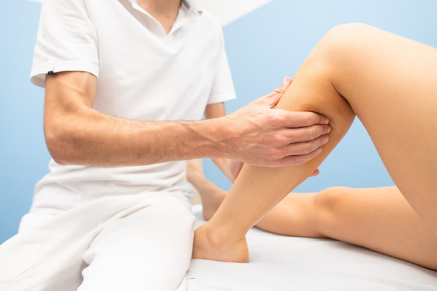 Massagem delicada na panturrilha no spa de um fisioterapeuta profissional