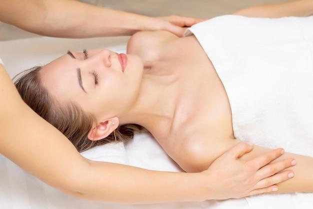 Massagem e cuidados com o corpo. spa massagem corporal mãos tratamento. mulher com massagem no salão spa para mulher bonita