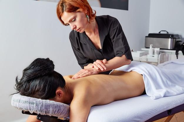 Massagem em mulher volta com fisioterapeuta