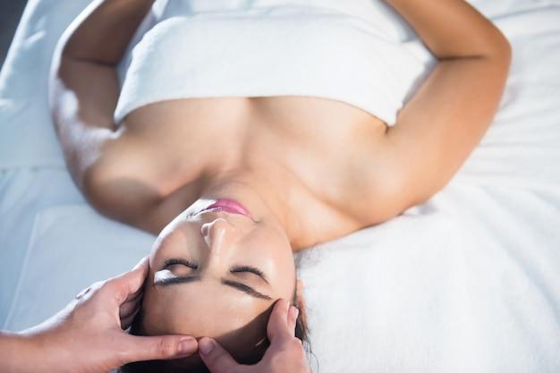 Massagem facial ayurvédica com óleo tailandês na cama para tratamento facial anti-envelhecimento de mulher jovem e bonita asiática