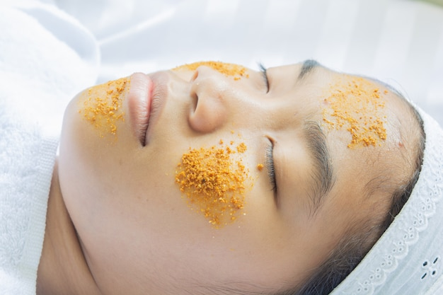 Massagem facial de cúrcuma e ingredientes de tamarindo. tratamento facial mel
