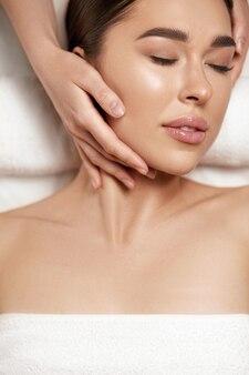 Massagem facial. linda de jovem recebendo tratamento de massagem de spa no salão de beleza spa. cuidados com a pele e o corpo de spa. tratamento de beleza facial.cosmetologia.