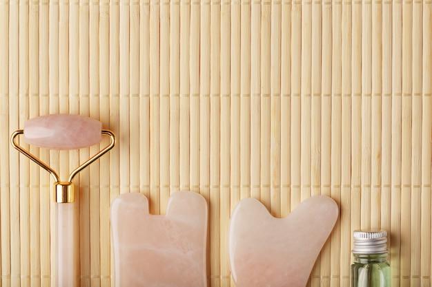Massagem gua sha feita de rolete de quartzo rosa natural, pedra jade e óleo, sobre um fundo de bambu para cuidados com o rosto e o corpo.