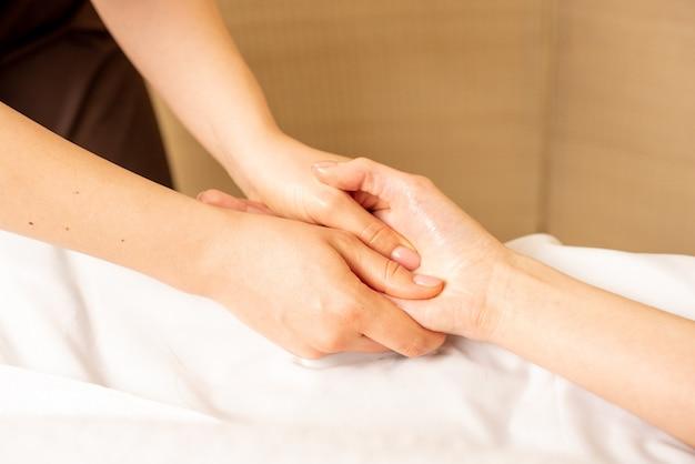 Massagem manual. fisioterapeuta pressionando pontos específicos na palma da mão feminina.