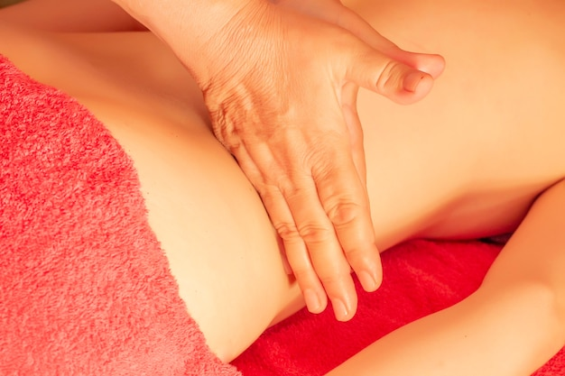 Massagem manual. garota está deitada no sofá e fazendo massagem nas mãos