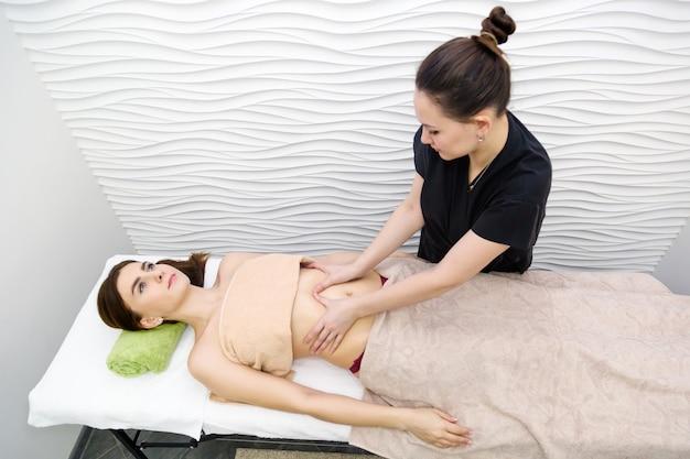 Massagem médica do abdômen no salão de beleza