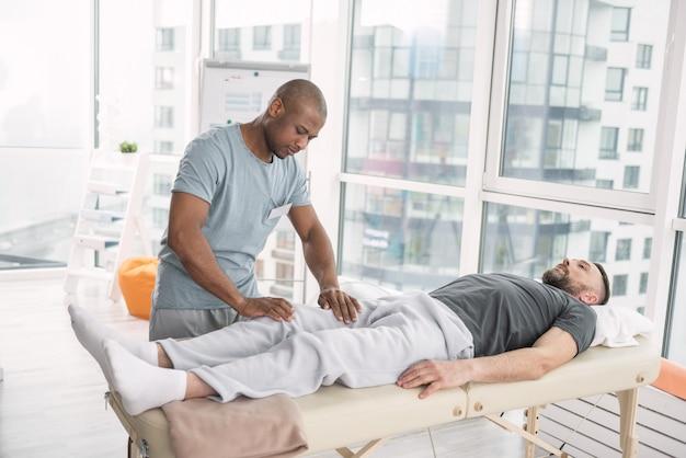 Massagem médica. homem inteligente e simpático em pé perto de seu paciente enquanto faz uma massagem para ele