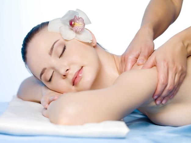 Massagem médica no ombro de uma jovem mulher bonita - horizontal