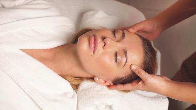 Massagem na cabeça e no rosto de uma mulher bonita em close-up, uma mulher cuidando do rosto